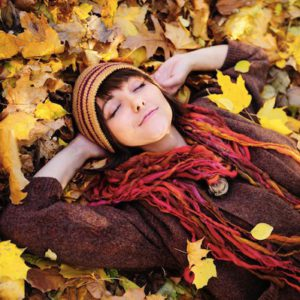 What is the best way to use the Law of Attraction: learn the rules! This woman might be memorizing what she learned while lying in a pile of autumn leafs